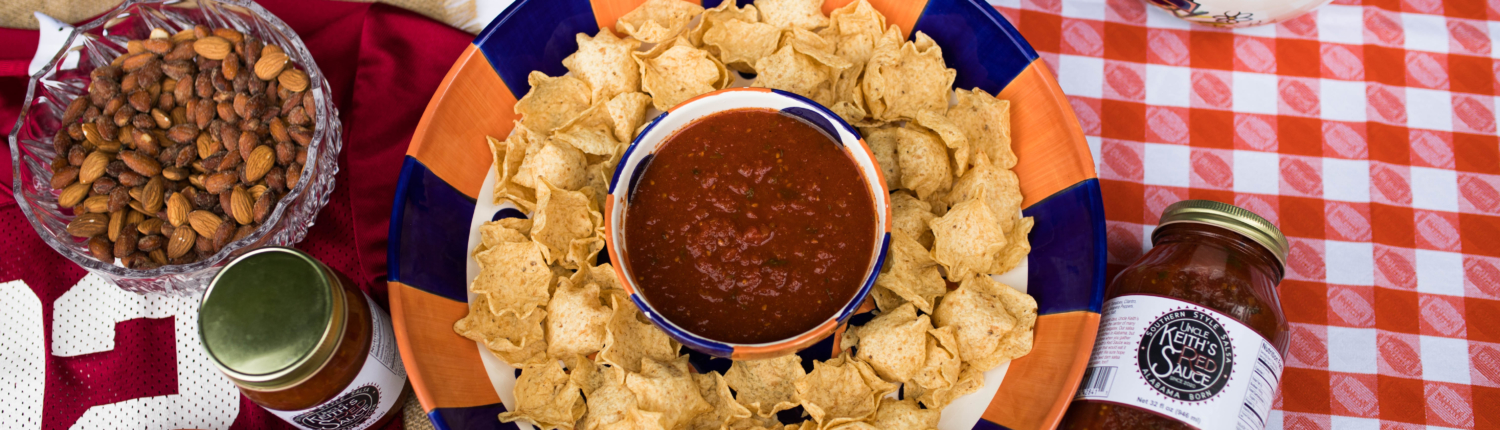 Tailgate table with nuts, grapes, brownies, chips, and Uncle Keiths Red Sauce Salsa
